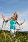 De blonde jonge rijpe vrouw oefent met hulahoepel uit Stock Afbeelding