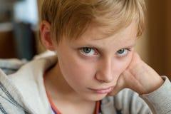 De blonde jongen kijkt met kwade ogen stock afbeeldingen