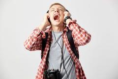 De blonde kerel in hoofdtelefoons, met zwarte rugzak op zijn schouders gekleed in een witte t-shirt en een rood geruit overhemd s stock foto