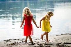 De blonde meisjes in rode kleding en gele kleding bij de rivier lopen vast Royalty-vrije Stock Afbeelding