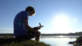 De blonde mens bekijkt familiefoto's op een meerbank in de zomer stock footage