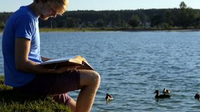 De blonde mens bekijkt foto's De eenden zwemmen dichtbij in een meer stock videobeelden