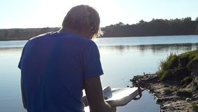 De blonde mens bekijkt zijn photoalbum op een meerbank stock footage