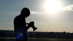 De blonde mens bevindt zich bij een bosmeer en bekijkt zijn camera in de zomer stock footage