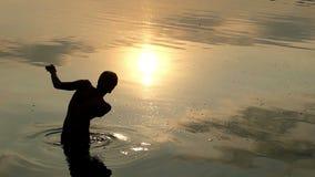 De blonde Mens bevindt zich in Rivierwater en werpt een Vlak Grint bij Zonsondergang stock videobeelden