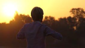 De blonde mens doet yogaoefeningen op een meerbank bij zonsondergang in slo-mo stock videobeelden
