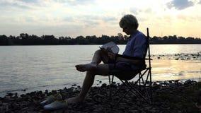 De blonde Mens gaat zitten en schrijft in Zijn Blocnote op Nice Riverbank stock video