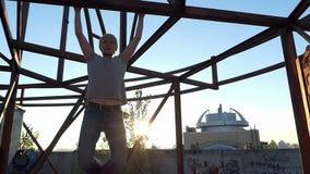 De blonde mens trekt op een bouwwerf uit bij zonsondergang in slo-mo stock footage