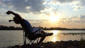 De blonde Mens zit, leest en schrijft Zijn Nota's over een Riverbank bij Zonsondergang stock videobeelden
