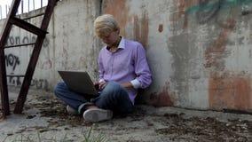 De blonde mens zit op een bouwwerf en werkt bij zijn laptop stock video