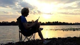 De blonde Mens zit op een Vouwende Stoel en bekijkt Zijn Tabletpc Zonsondergang stock footage