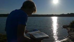 De blonde mens zit in profiel en bekijkt foto's op een meerbank stock videobeelden
