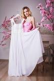 De blonde mooie vrouw houdt haar huwelijkskleding Royalty-vrije Stock Foto's