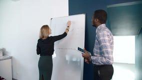De blonde onderneemster legt het plan aan haar Afro-Amerikaanse mannelijke collega voor stock videobeelden