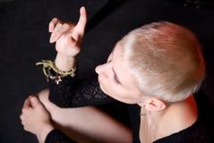 De blonde richt naar omhoog een vinger Stock Fotografie