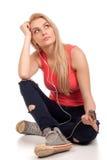 De blonde tienerzitting en luistert muziek Royalty-vrije Stock Foto's