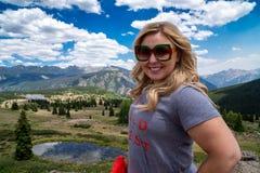 De blonde volwassen vrouw stelt bij Molas-Pas langs de Miljoen dollarweg in San Juan Mountains van Colorado de V.S. stock foto's