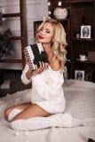 De blonde vrouw draagt comfortabele gebreide cardigan, die naast Kerstboom stellen royalty-vrije stock afbeelding