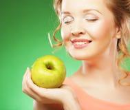 De blonde vrouw eet groene appel over groene achtergrond stock foto's