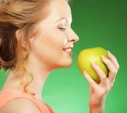 De blonde vrouw eet groene appel over groene achtergrond stock afbeeldingen