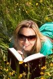 De blonde vrouw met elektrische sigaret leest een boek Stock Foto