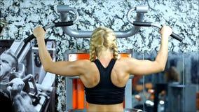 De blonde vrouw met rode borrels en zwarte hoogste oefeningen op het gymnastiekmateriaal stock videobeelden