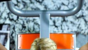 De blonde vrouw met rode borrels en zwarte hoogste oefeningen op het gymnastiekmateriaal stock footage