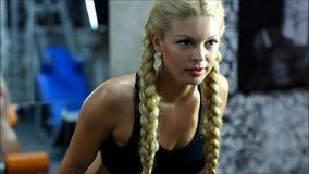 De blonde vrouw met rode borrels en zwarte hoogste oefeningen op het gymnastiekmateriaal stock video