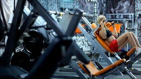 De blonde vrouw op de materiaalgymnastiek stock footage