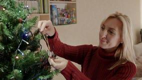 De blonde vrouw in rode trui verfraait Kerstboom met dichte omhooggaand van Kerstmisherten stock footage
