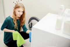 De blonde vrouw zette vuile kleren in de wasmachine stock fotografie