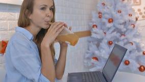 De blonde Vrouwenglimlachen drinkt Sap dichtbij Moderne Laptop stock video