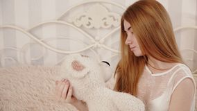 De blondebruid in negligé kijkt en koestert teddybeer stock video