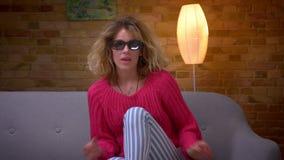 De blondehuisvrouw die in roze sweater en 3D glazen verschrikkings op film letten wordt angst aangejaagd en doet leunen op bank b stock footage