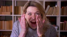 De blondeleraar op middelbare leeftijd toont sterk vermaak en geluk in het gezicht van camerainhammen met handen bij de bibliothe stock video