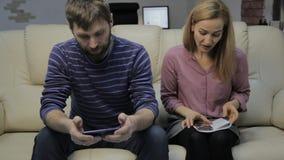 De blondestudent leest haar nota's, en haar vriendzitting op bank en gebruik smartphones stock footage