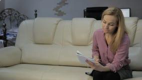 De blondestudent leest haar nota's, voorbereidingen treft om examens op een bank thuis te nemen stock videobeelden