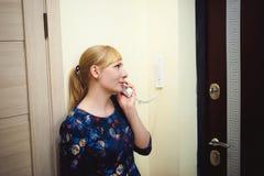 De blondevrouw beantwoordt intercomvraag, houdt de telefoon aan zijn oor stock foto