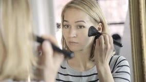 De blondevrouw die dagelijkse make-up voor spiegel doen, zet poeder op haar wangen met borstel stock footage