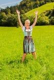 De blondevrouw in een dirndl is gelukkig in een groene weide Royalty-vrije Stock Foto
