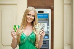 De blondevrouw in een groene kleding houdt een contant gelddollars Royalty-vrije Stock Fotografie