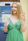 De blondevrouw in een groene kleding houdt een contant gelddollars Royalty-vrije Stock Afbeelding