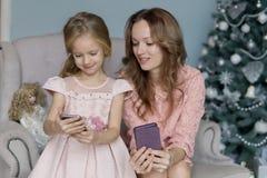 De blondevrouw in een roze blouse zit op bank en houdt een mobiele telefoon in een purper geval naast dochter 5 jaar oude blikken royalty-vrije stock fotografie