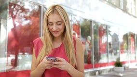 De blondevrouw in een roze t-shirt gebruikt haar mobiele telefoon en glimlach dichtbij het stadscentrum stock video