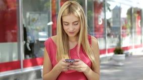 De blondevrouw in een roze t-shirt gebruikt haar mobiele telefoon en glimlach dichtbij het stadscentrum stock videobeelden