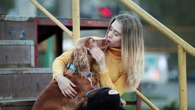 De blondevrouw en de hondcocker-spaniël strijken de de kussenglimlachen van hondzorgen in de avond in stad stock footage