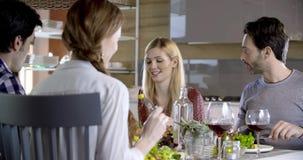 De de blondevrouw en man die Vier gelukkige echte spontane vrienden spreken genieten hebbend lunch of diner samen thuis van of re stock videobeelden