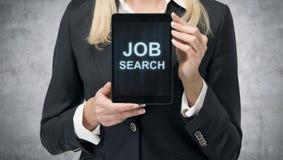 De blondevrouw in formeel kostuum stelt een tablet met de woorden 'Job Search' op het scherm voor Een concept rekruteringsproces  Royalty-vrije Stock Afbeeldingen