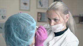 De blondevrouw maakt brow tatoeërend op cliëntgezicht in kliniek stock videobeelden