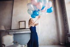 De blondevrouw met ballons viert iets Stock Foto